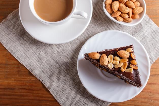Schokoladenkuchen mit karamell, erdnüssen und mandeln auf einem braunen hölzernen hintergrund.