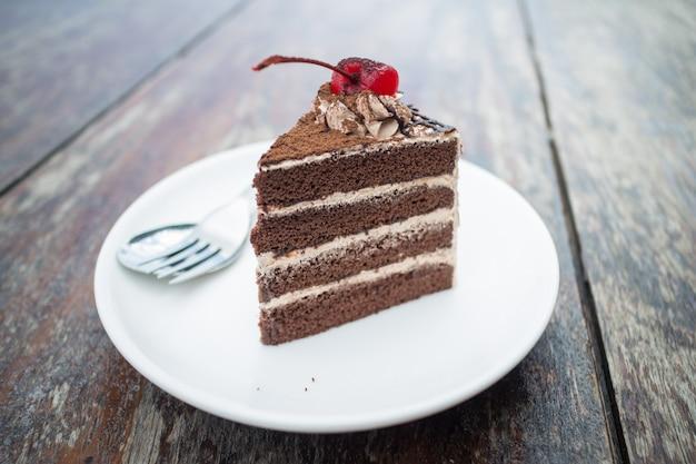 Schokoladenkuchen mit kirschbelag im gemütlichen café im freien