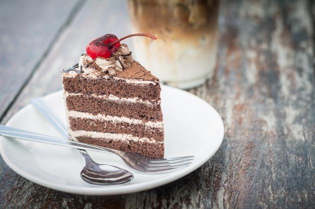 Schokoladenkuchen mit kirschbelag und eiskaffeemokka café im im freien