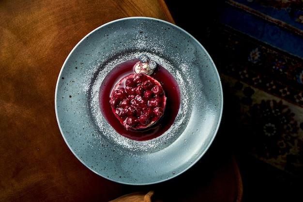 Schokoladenkuchen mit kirschen und marmelade, pudding, serviert in einem blauen teller. restaurant serviert dessert