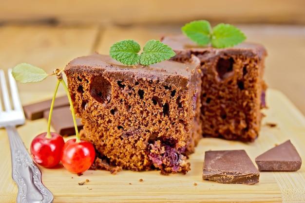 Schokoladenkuchen mit kirschen und minze, gabel auf dem hintergrund von holzbrettern