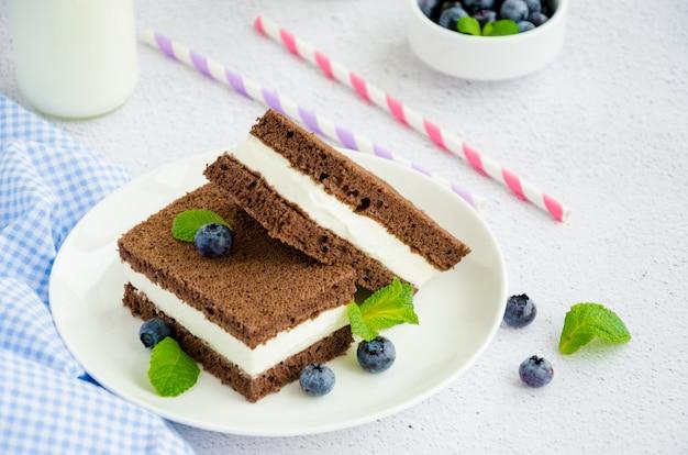 Schokoladenkuchen mit milchcremefüllung auf einem weißen teller mit frischen blaubeeren und minze