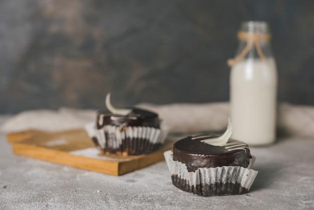 Schokoladenkuchen mit milchflasche auf konkretem beschaffenheitshintergrund
