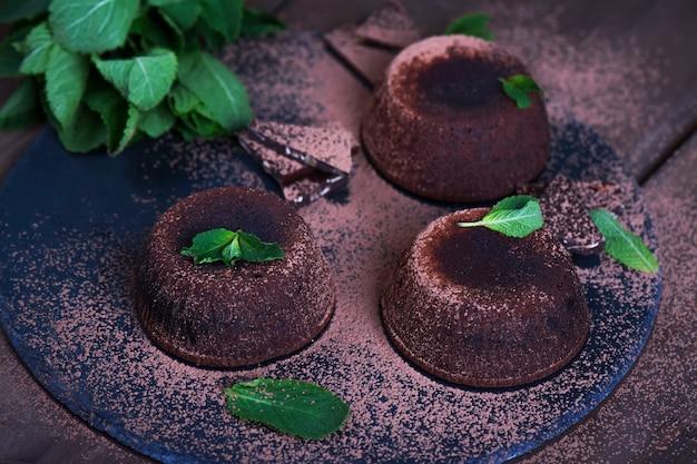 Schokoladenkuchen mit minze. schokoladenkuchen mit dunkler schokolade und tadellosen blättern auf dunklem hintergrund.