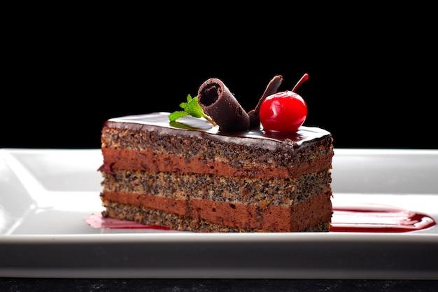 Schokoladenkuchen mit mohn. auf einem weißen teller, auf einem dunklen tisch