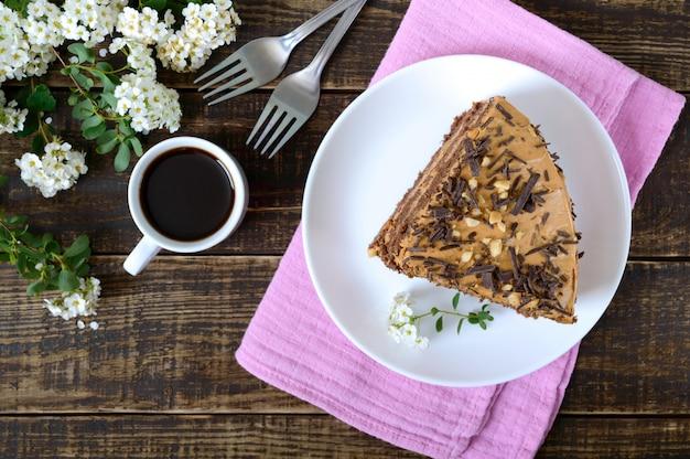 Schokoladenkuchen mit nusscreme auf einem holztisch. ein stück kuchen auf einem teller und eine tasse kaffee. die draufsicht