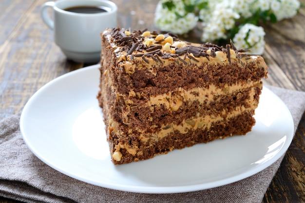 Schokoladenkuchen mit nusscreme auf einem holztisch. ein stück kuchen auf einem teller und eine tasse kaffee.