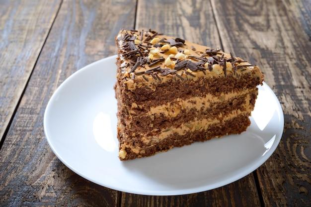 Schokoladenkuchen mit nusscreme auf einem holztisch. ein stück kuchen auf einem teller