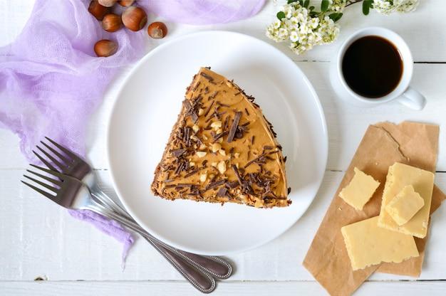 Schokoladenkuchen mit nusscreme auf einem weißen holztisch. ein stück kuchen auf einem teller und eine tasse kaffee. die draufsicht