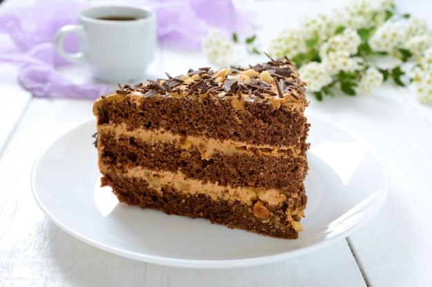 Schokoladenkuchen mit nusscreme auf einem weißen holztisch. ein stück kuchen auf einem teller und eine tasse kaffee.