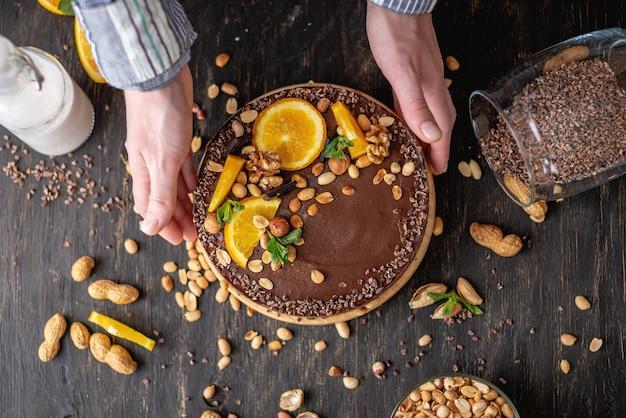 Schokoladenkuchen mit orange, kakao, minzblättern, erdnüssen und nüssen