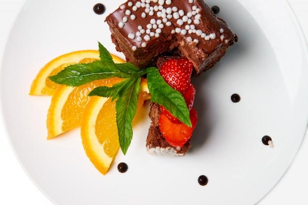 Schokoladenkuchen mit orange und erdbeeren auf einem weißen teller.