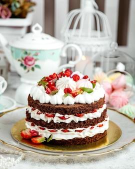Schokoladenkuchen mit schlagsahne und früchten
