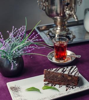 Schokoladenkuchen mit schwarzem tee auf dem tisch