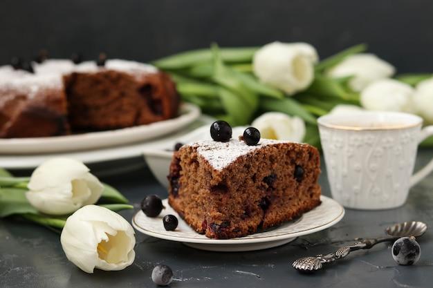 Schokoladenkuchen mit schwarzer johannisbeere, auf dem tisch steht eine tasse kaffee und weiße tulpen