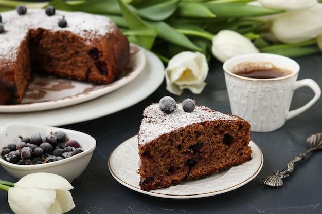 Schokoladenkuchen mit schwarzer johannisbeere auf einer dunklen, auf dem tisch steht eine tasse kaffee und weiße tulpen