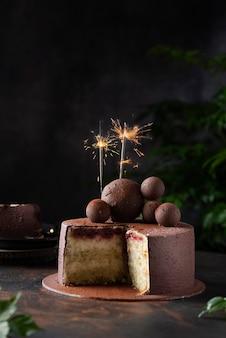 Schokoladenkuchen mit weihnachtswunderkerzen auf einem dunklen hintergrund, selektives fokusbild