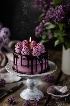 Schokoladenkuchen und ein fliederstrauß auf holztisch