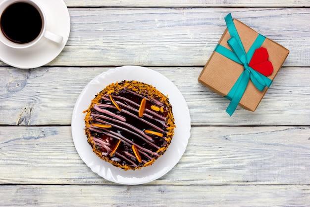 Schokoladenkuchen und geschenk in bastelpapier mit einer notiz in form eines roten herzens eingewickelt. von oben betrachten.