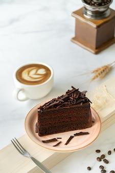Schokoladenkuchen und kaffee. schokoladenkuchen auf rosa platte. kuchen auf weißem marmorhintergrund.