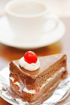 Schokoladenkuchen und kaffeetasse im hintergrund