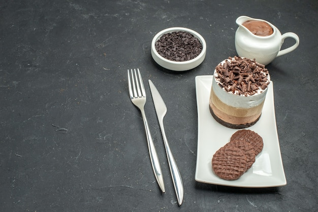 Schokoladenkuchen und kekse von unten auf weißer rechteckiger tellerschüssel mit schokoladengabel und -messer auf dunklem, isoliertem hintergrund mit freiem platz
