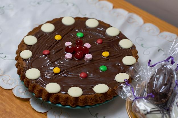 Schokoladenkuchen und korb mit ostereiern, eingewickelt in transparentes papier