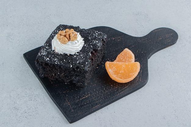 Schokoladenkuchen und marmeladen auf einer schwarzen tafel auf marmorhintergrund.