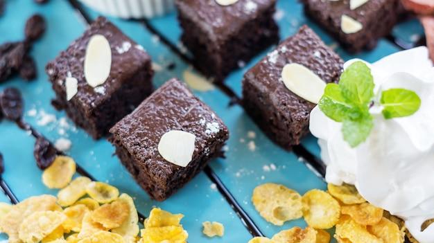 Schokoladenkuchen und peitschencreme auf einer blauen platte.