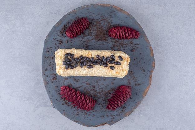 Schokoladenkuchen und rote tannenzapfen auf einem holzbrett auf marmortisch.