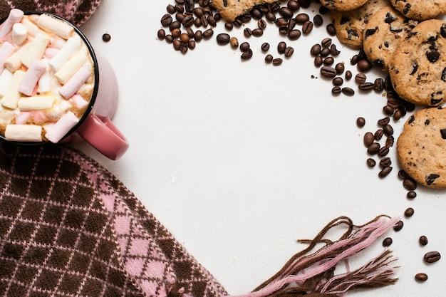 Schokoladenkuchen und tasse latte mit marshmallow, warmer, gemütlicher schal in der nähe, draufsicht, freier platz in der mitte. köstlicher kalter morgen mit keksen und heißem getränk