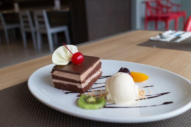 Schokoladenkuchen und vanilleeis mit frischem obst und kirsche