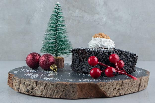 Schokoladenkuchen und weihnachtsdekorationen auf einem holzbrett auf marmorhintergrund.