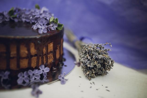 Schokoladenkuchen verziert mit blumen von flieder und lavendel auf violettem hintergrund