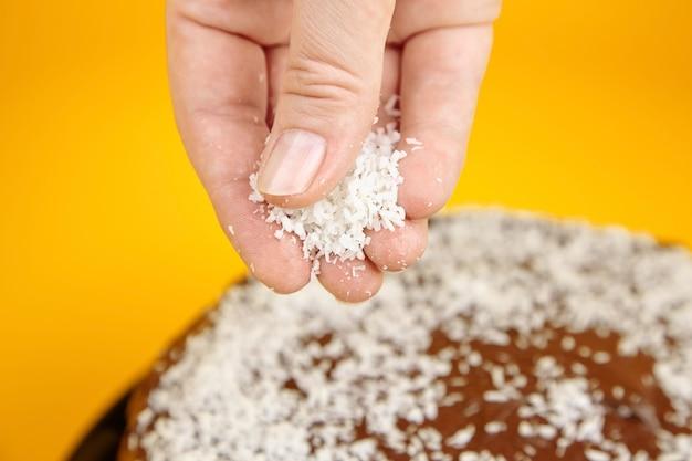 Schokoladenkuchen verziert mit kokosflocken, hausgemachter kuchen auf gelber oberfläche. femake hand, die kokosflocken streut. hauptkuchen mit kakaobestandteil auf schwarzer keramikplatte, selektiver fokus