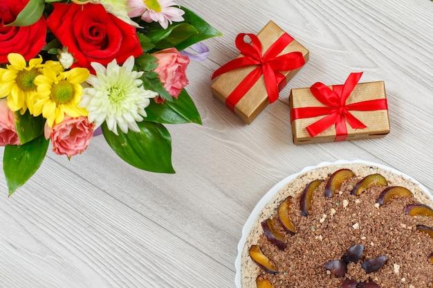 Schokoladenkuchen verziert mit pflaumen, einem blumenstrauß und geschenkboxen auf den grauen holzbrettern. ansicht von oben.