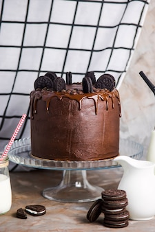Schokoladenkuchen verziert mit plätzchen auf einem glasstand