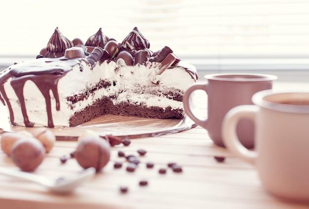Schokoladenkuchen verziert mit pralinen mit macadamianüssen und zwei tassen kaffee