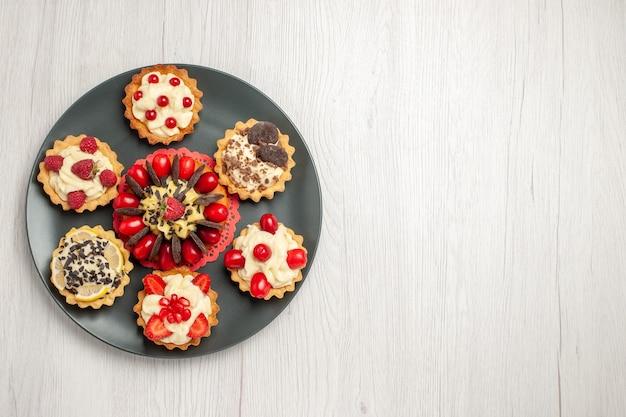 Schokoladenkuchen von oben links, abgerundet mit beerentörtchen in der grauen platte in der mitte des weißen holztischs
