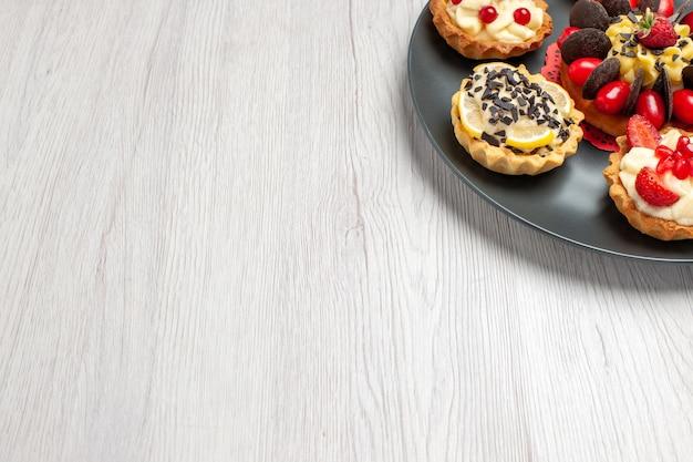 Schokoladenkuchen von oben rechts, abgerundet mit beerentörtchen in der grauen platte oben rechts auf dem weißen holztisch