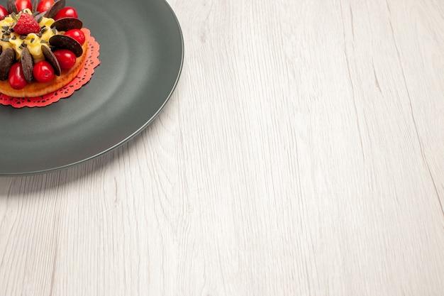 Schokoladenkuchen von unten links, abgerundet mit kornelkirsche und himbeere in der mitte in der grauen platte auf dem weißen hölzernen hintergrund