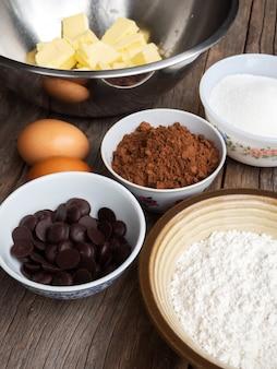 Schokoladenkuchenbestandteile auf holztisch. draufsicht mit exemplar.