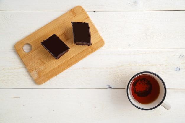 Schokoladenkuchenkuchen auf einem bambusbehälter mit tasse tee auf einem weißen hölzernen hintergrund mit raum für text