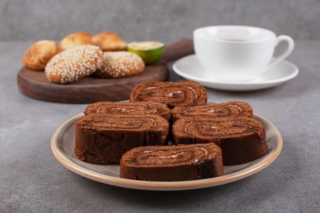Schokoladenkuchenrolle auf keramikplatte mit schwarzem tee