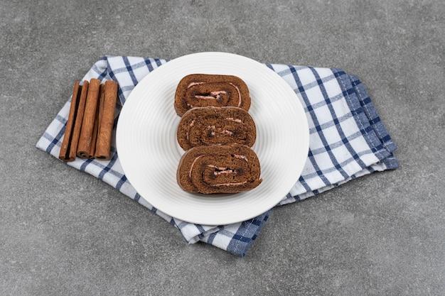 Schokoladenkuchenrolle auf weißem teller mit zimt