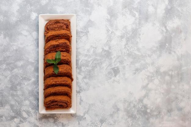 Schokoladenkuchenrolle mit kakaopulver auf weißer platte, draufsicht