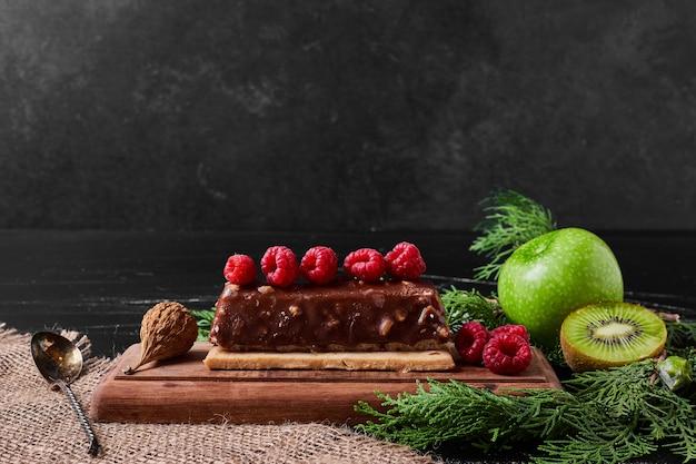 Schokoladenkuchenscheibe auf einer holzplatte.