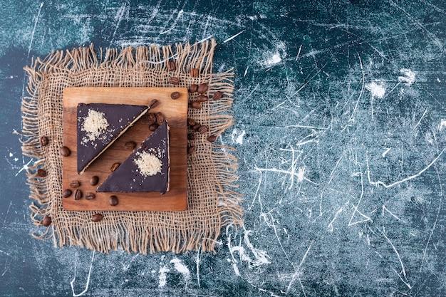 Schokoladenkuchenscheibe mit kaffeebohnen auf sackleinenoberfläche gelegt.