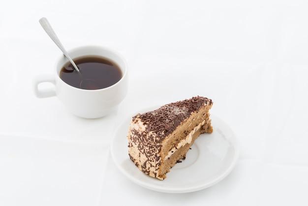 Schokoladenkuchenscheibe mit rotation auf weißem teller mit heißem getränk