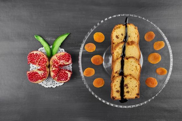 Schokoladenkuchenscheiben auf einer glasplatte mit früchten.
